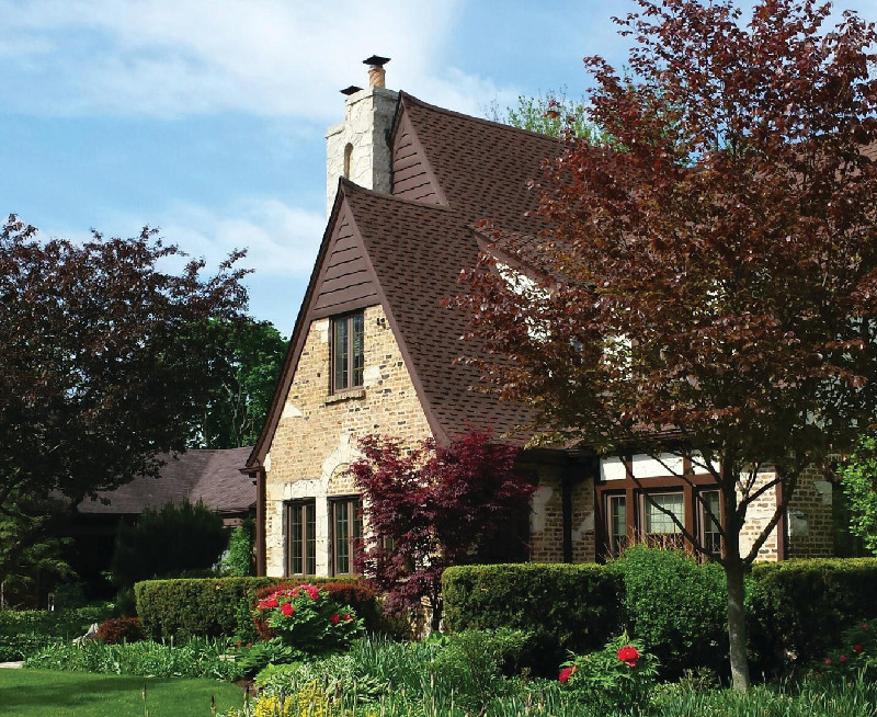 English tudor home in Chicago home with dark brown roof and spacious garden