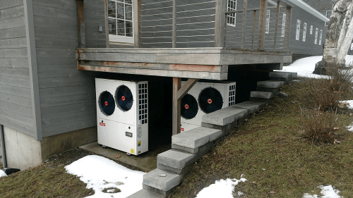 Two Solstice heat pumps under an elevated wooden deck with snow around