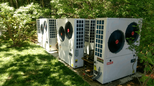 Four Hydronic Solstice heat pumps hidden in a backyard by trees and bushes
