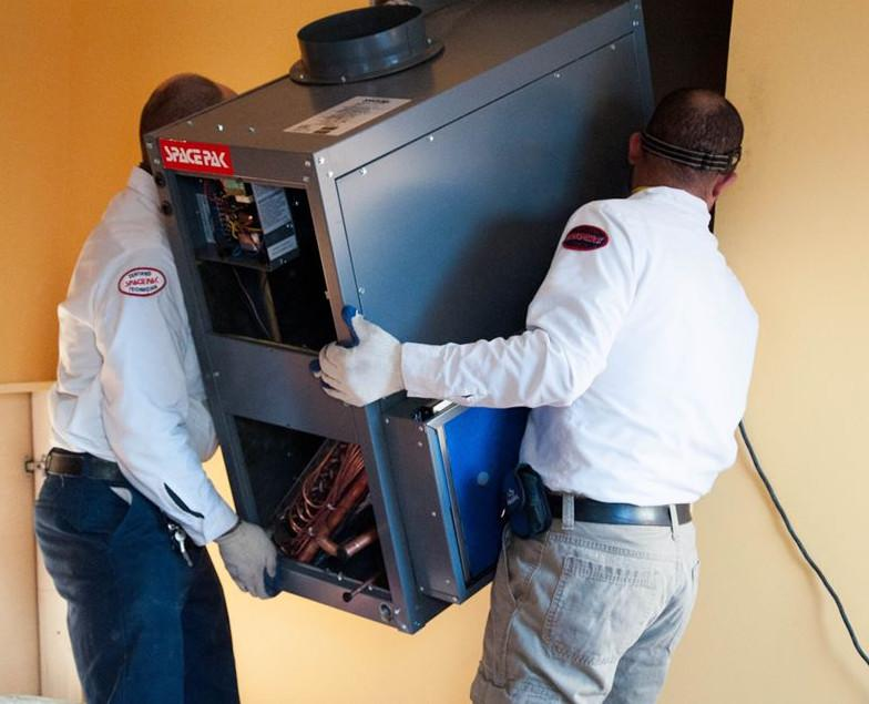 Two certified SpacePak contractors installing a SpacePak air unit