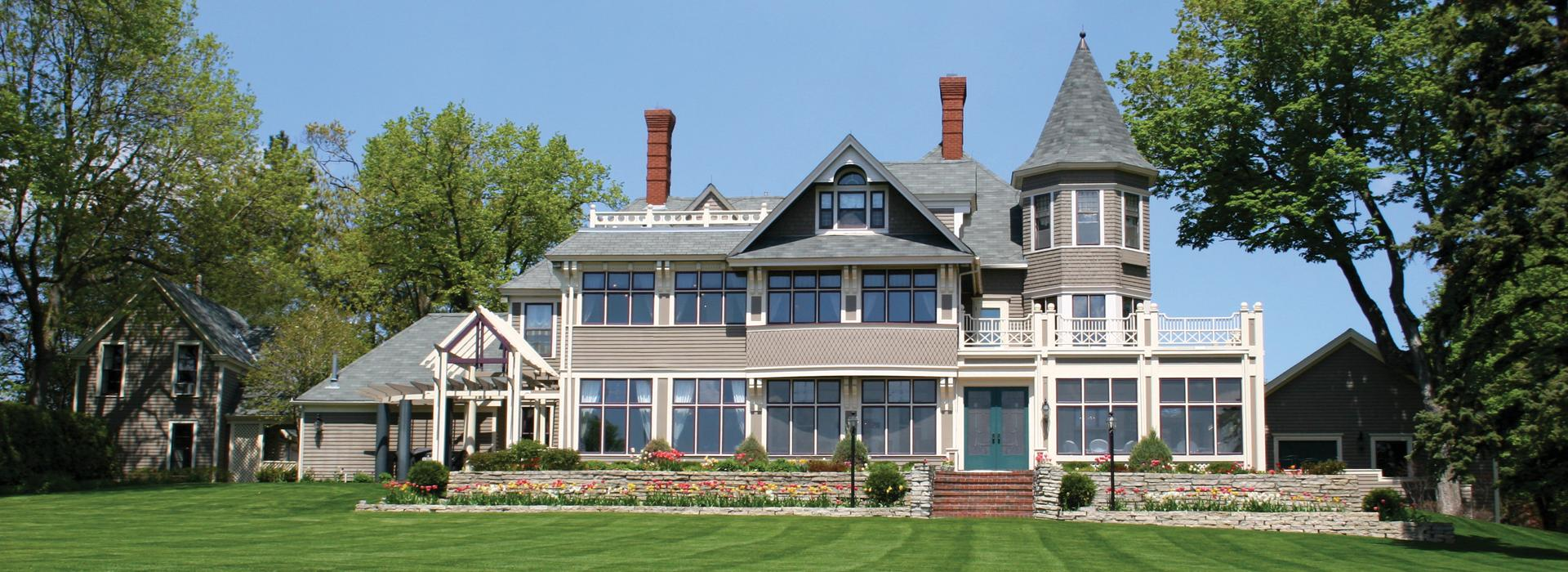 Colonial home with grey exterior, large windows, and manicured lawn with flowers